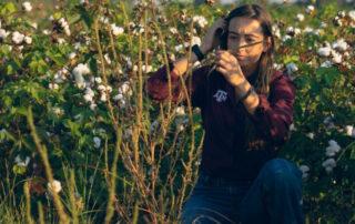 FFAR Fellow, Sarah Kezar kneeling in a cotton field.